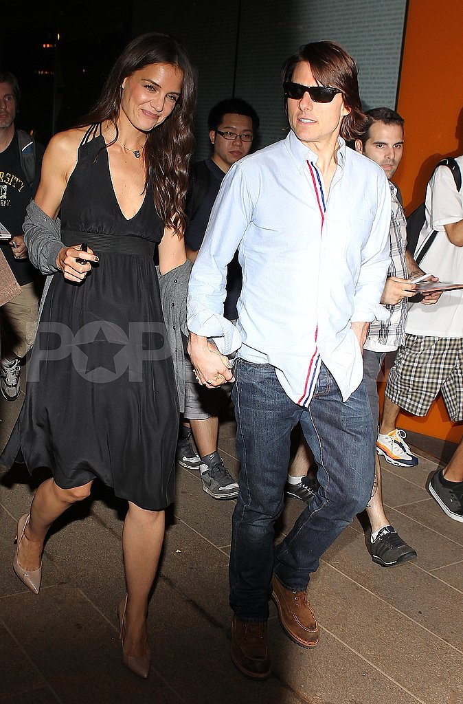 Katie Holmes and Tom Cruise hold hands.