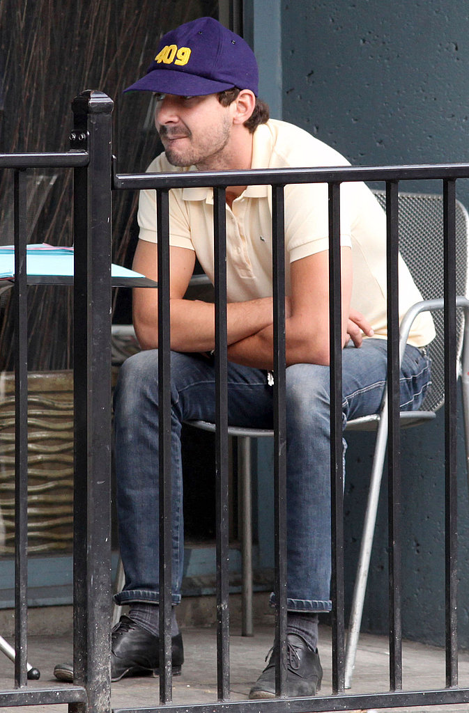 Shia dressed in a casual polo and blue hat for his coffee shop meeting.
