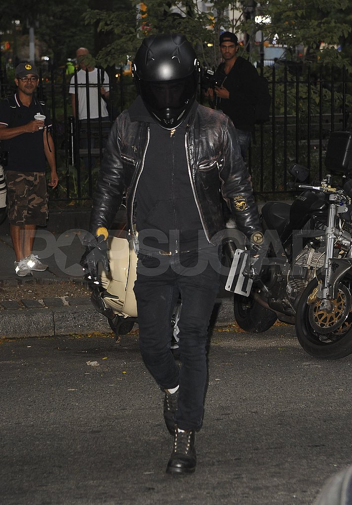 Justin Theroux hops off his motorcycle.