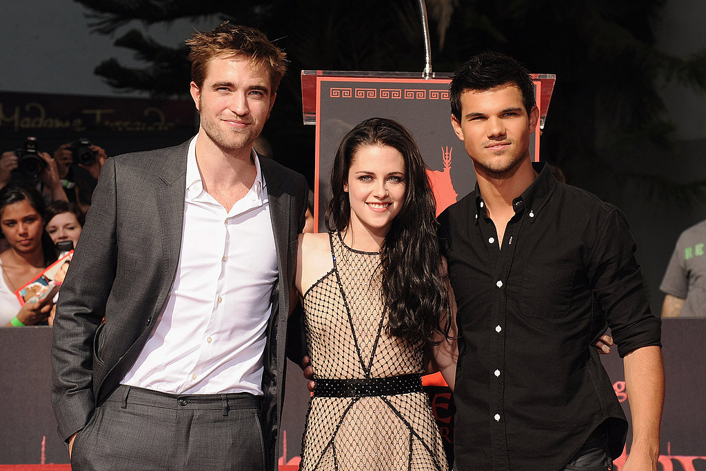 Robert Pattinson and Taylor Lautner put their arms around Kristen Stewart.