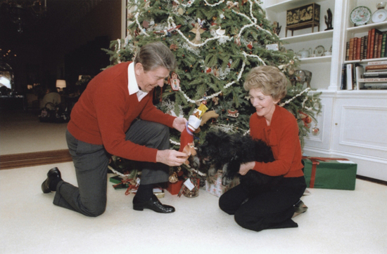 Former President Ronald Reagan and first lady Nancy Reagan cuddle up with Lucky under the tree in 1984 Source: Ronald Reagan Presidential Library