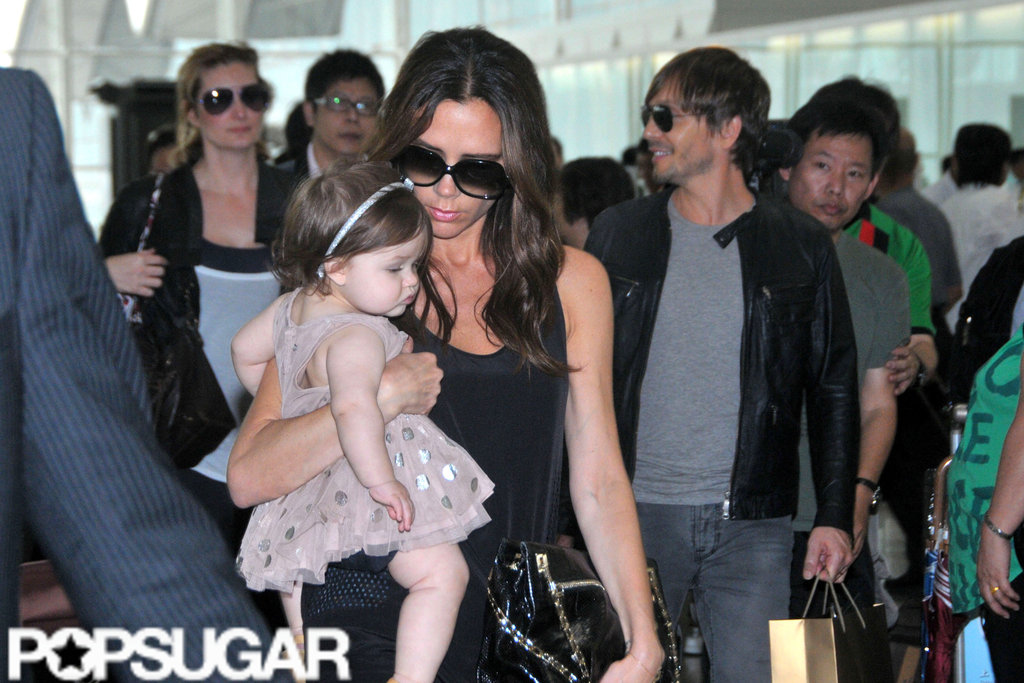 Victoria Beckham carried daughter Harper Beckham at the Hong Kong airport.