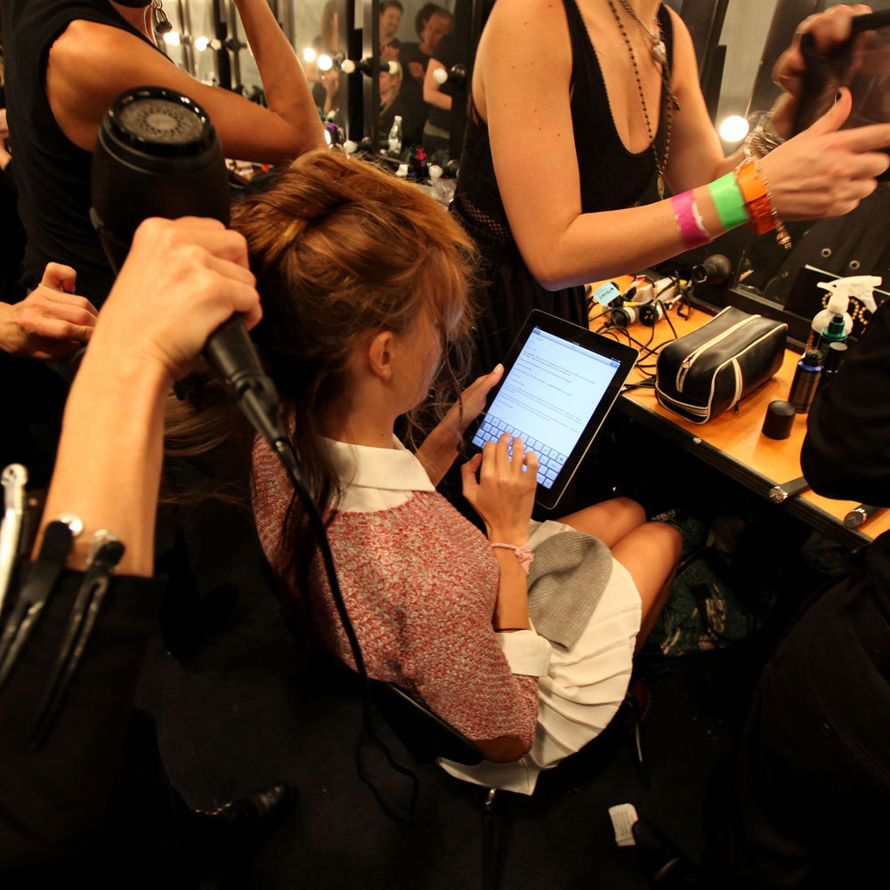 A model plays on her iPad while getting her hair done.
