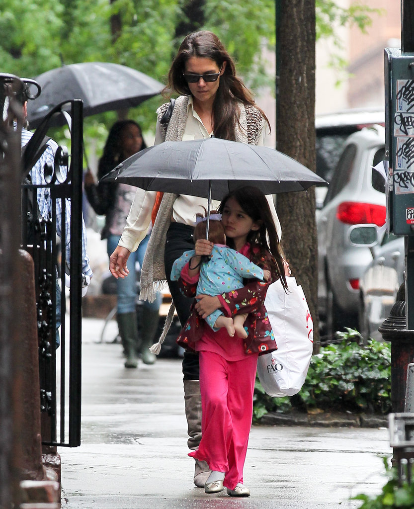 Suri Cruise protected her baby doll from the rain while Katie Holmes followed.