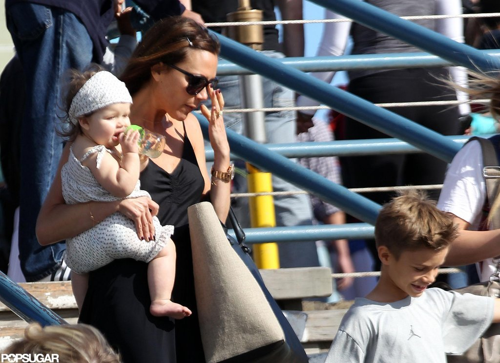 Victoria Beckham carried daughter Harper Beckham with son Romeo Beckham.