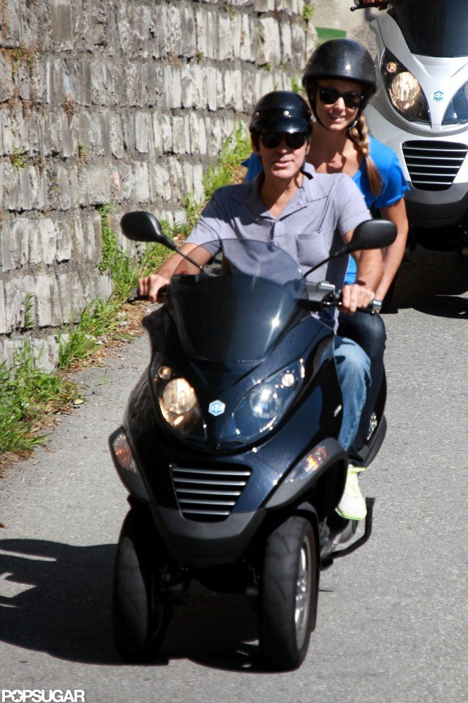Both George Clooney and Stacy Keibler donned black sunglasses and helmets for a scooter ride in Switzerland in July 2012.