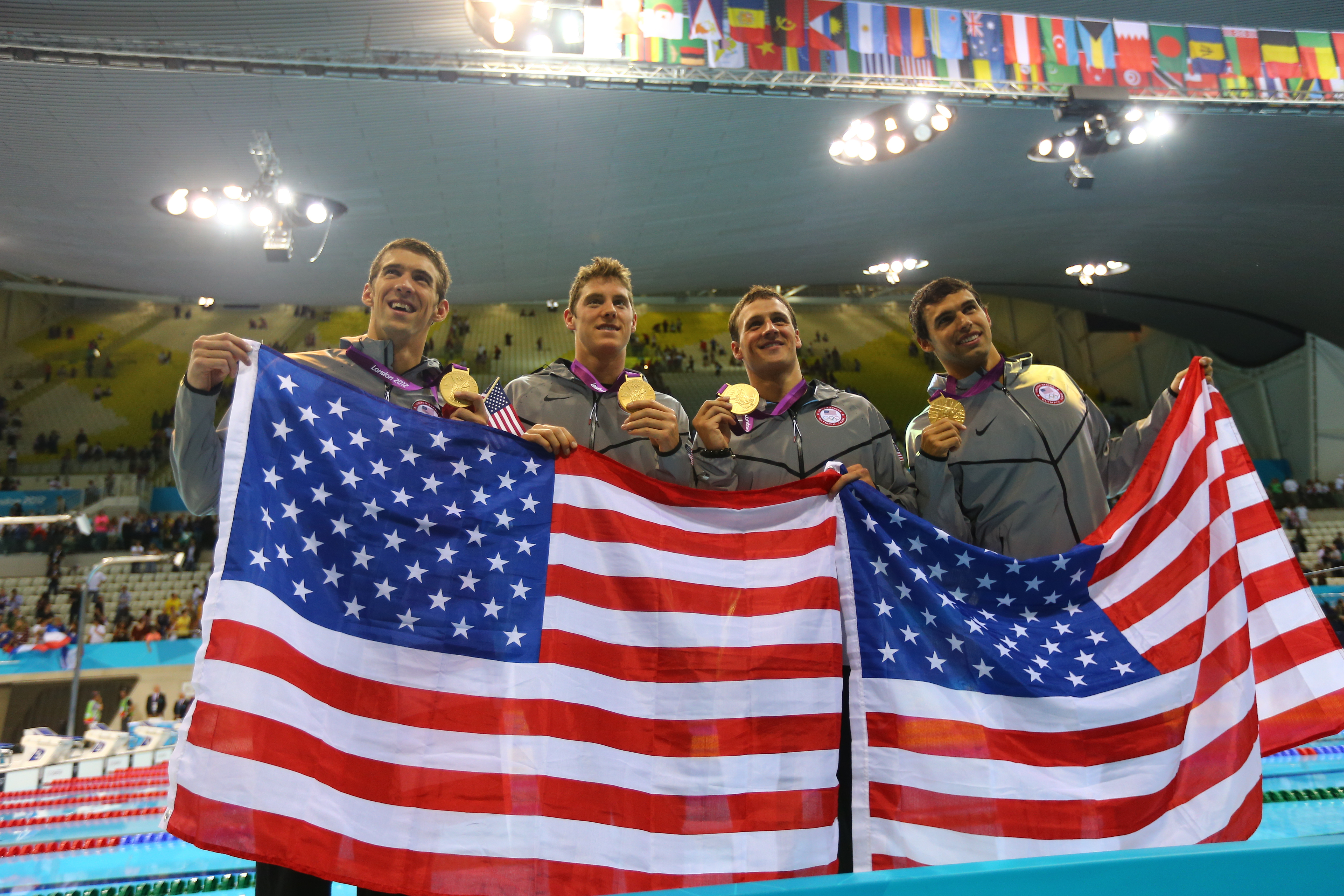 Michael Phelps posed for photos with his fellow gold medal winning relay teammates Ryan Locte, Ricky Berens, and Conor Dwyer.