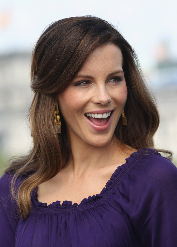 She accented her romantic purple Zac Posen dress with gold pendant earrings.