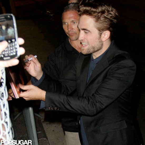 Robert Pattinson happily signed autographs for fans.