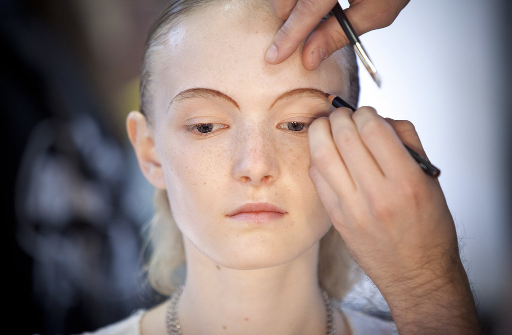 "Although bold brows have been a recent trend, key makeup artist Diane Kendal went for a thin and rounded brow look. She drew a guideline using NARS Mambo Eyeliner Pencil. ""Even though we didn't conceal the eyebrow, the eye goes to the smudged line,"" she explained."
