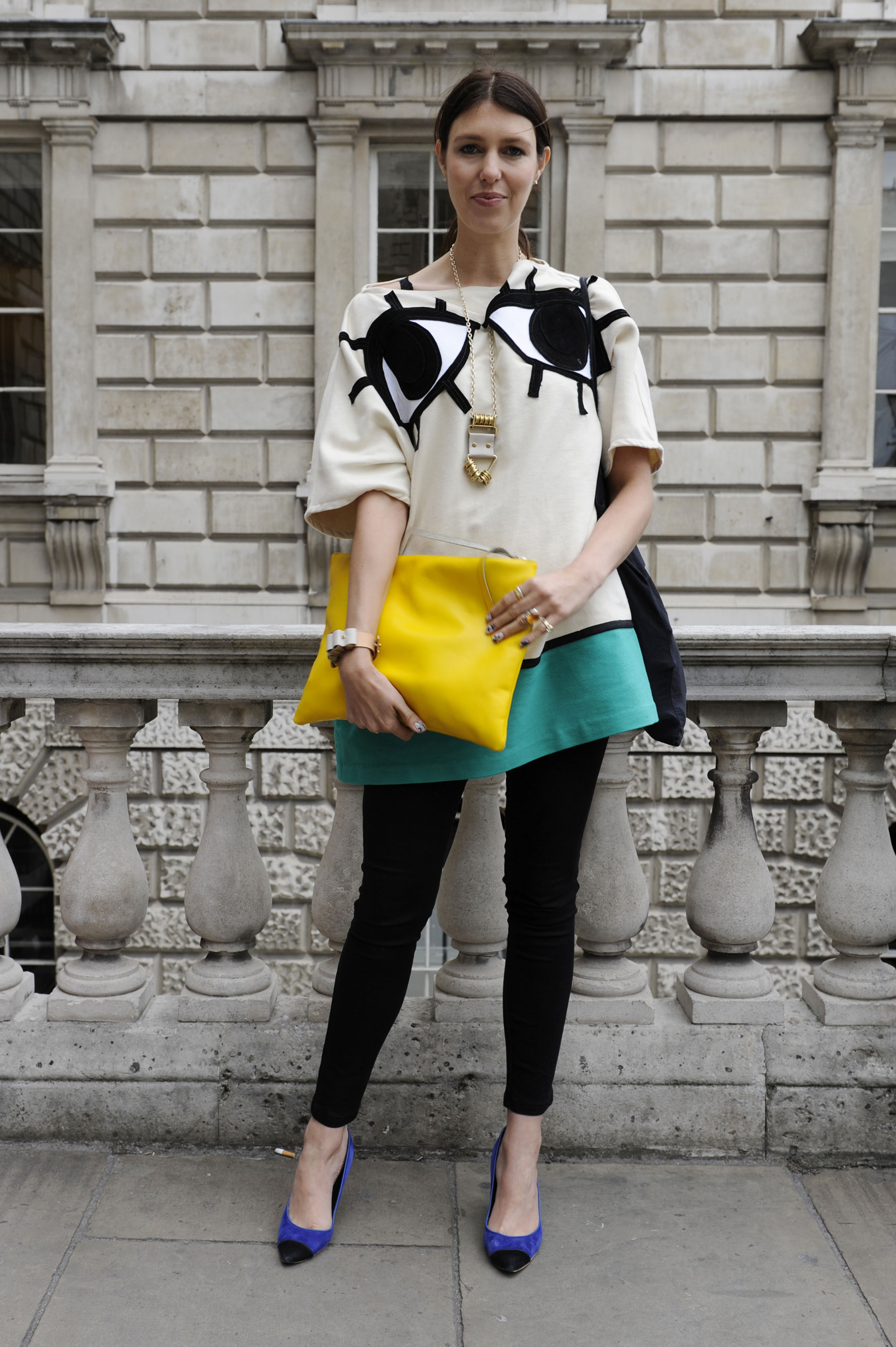 """Nothing says """"statement"""" like an eye-embroidered topper, yellow clutch, and electric blue pumps."""
