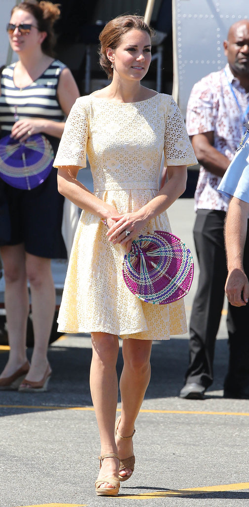 Kate Middleton, en route to Tuvalu, donned a daisy-eyelet dress in the pretty shade of pastel lemon by a yet-to-be-discovered independent designer. She complemented the look with her Stuart Weitzman sandal wedges and a colourful fan.