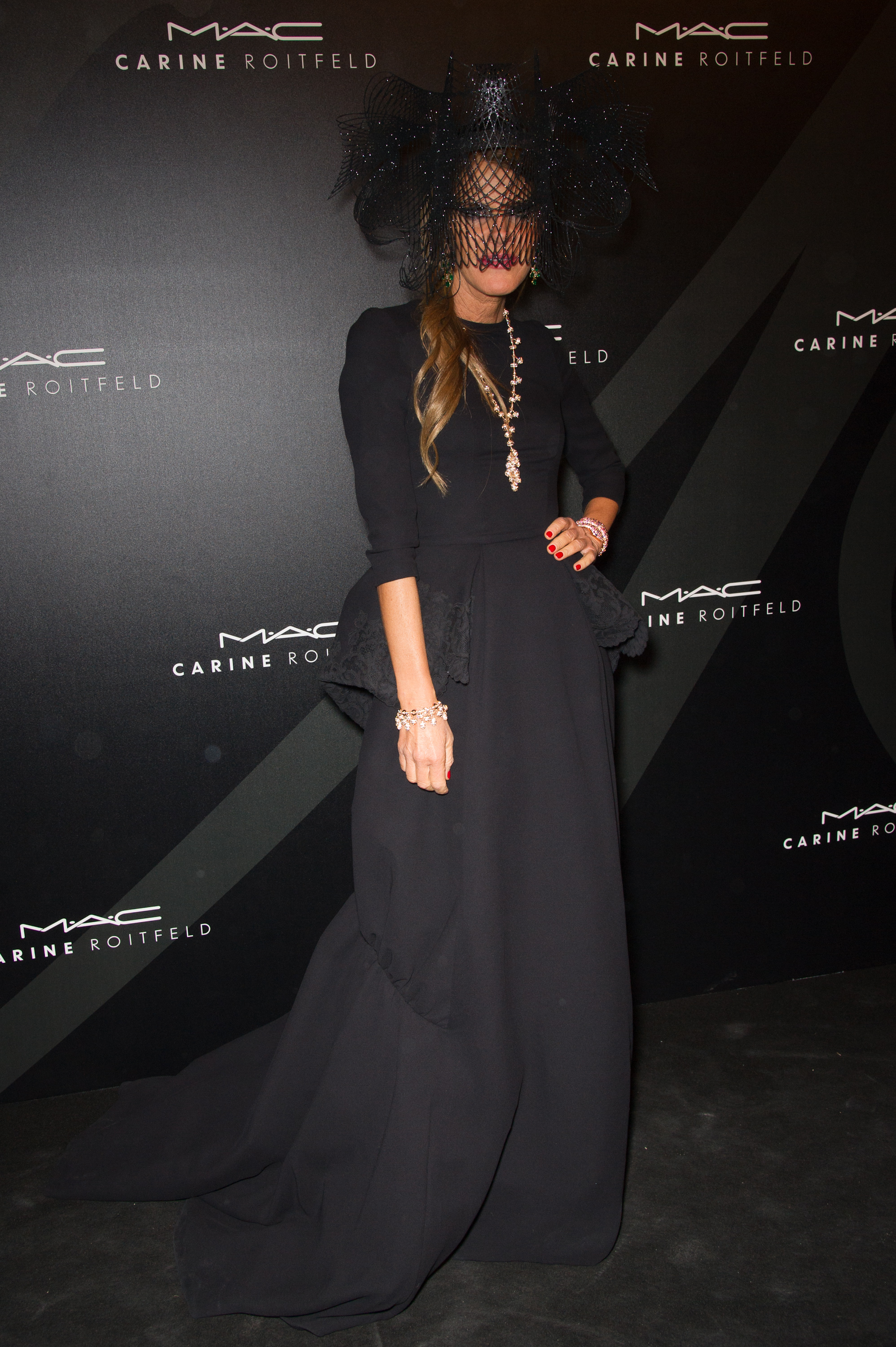 Anna Dello Russo opted for an ultradramatic vibe complete with a lace veil and statement jewelry at Carine's MAC party.