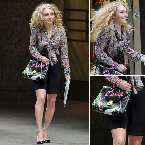 "Carrie worked a floral tie-neck blouse by 10 Crosby Derek Lam with loose black shorts, matching pumps, and a custom monogrammed ""Carrie"" bag while strolling around NYC."