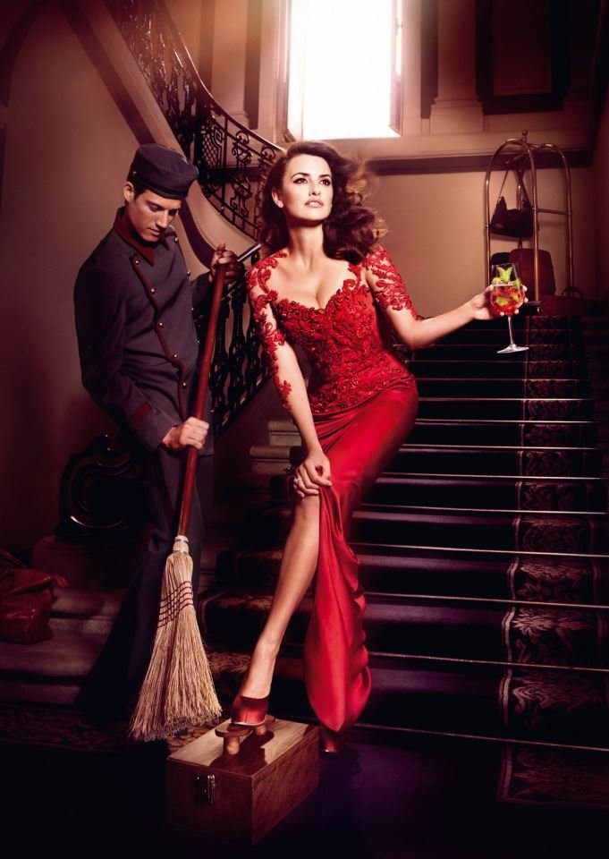 """Penélope Cruz wore a red lace Marchesa gown and acted out the """"passing the broom above the feet"""" superstition for Campari's 2013 calendar."""