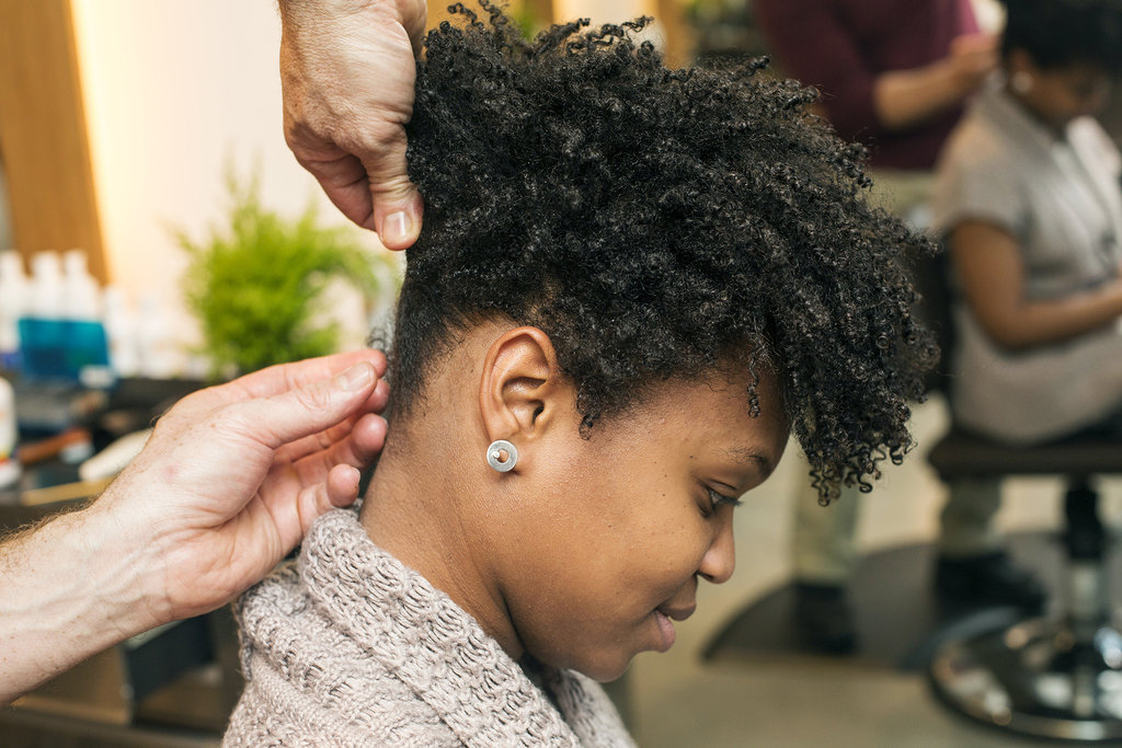 Continue to twist and pin all around the head. Don't worry about parting hair perfectly. Just grab and go. All the twists should end near one central point at the crown of the head. In order to keep the twists smooth and flyaways scarce, use a pomade on your fingers as you style.