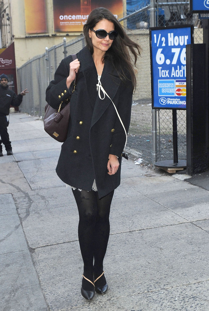Katie Holmes winterized a little dress with a military-style coat and black tights.