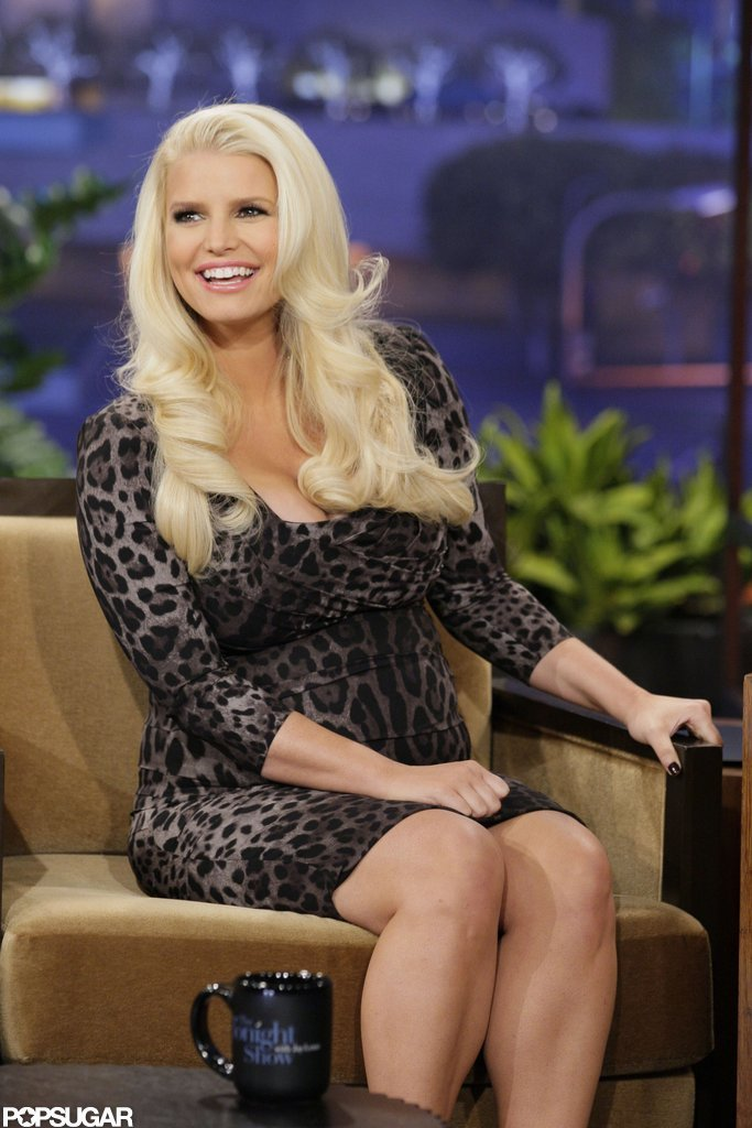 """Pregnant Jessica Simpson wore a low-cut dress for an appearance on The Tonight Show, during which she said she and fiancé Eric Johnson """"had two different wedding dates, but he keeps knocking me up!"""""""