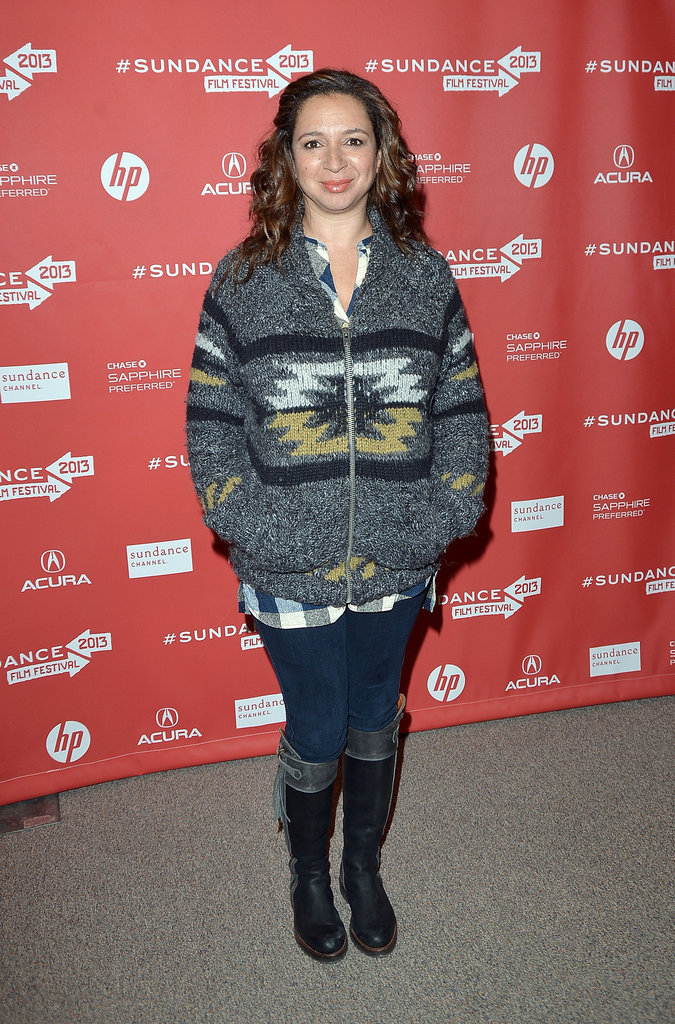 Maya Rudolph cosied up in a printed zip-up sweater, a plaid flannel blouse, and two-toned leather boots.