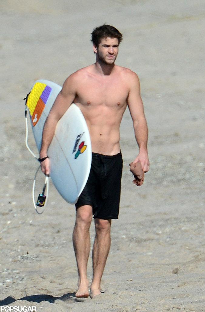 Liam Hemsworth went shirtless to go surfing in Costa Rica.