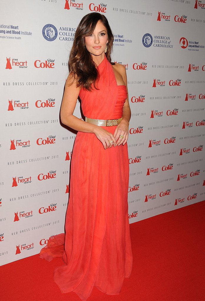 Minka Kelly donned a red Oscar de la Renta halter gown with a gold belt and gold drop earrings at the Heart Truth fashion show at New York Fashion Week.