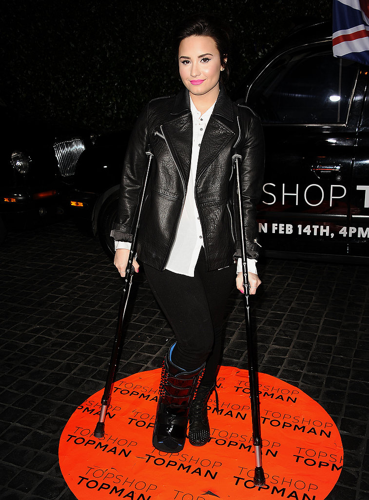 Demi Lovato didn't let her crutches slow her down. The singer chose a edgier leather jacket to go with her studded boots.