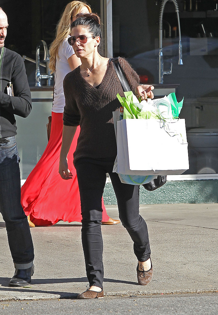 Sandra Bullock sported sunglasses with her hair up in a bun.