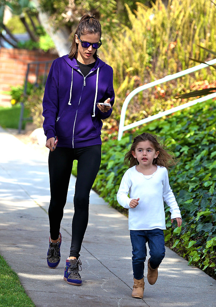 Alessandra Ambrosio checked her phone as daughter Anja walked in front of her.