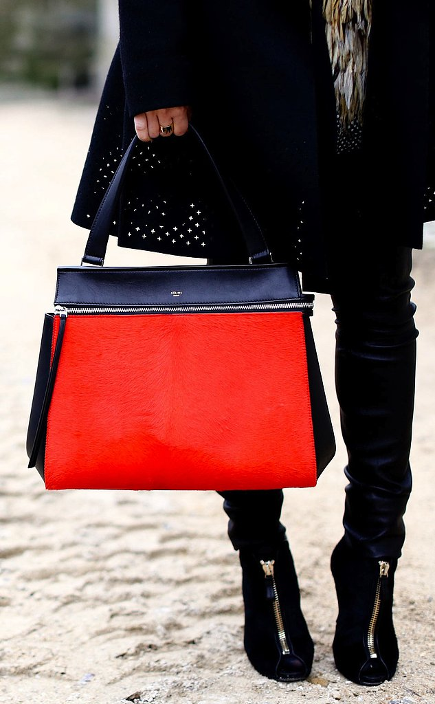 A Fashion Week attendee paired her dark accompaniments with a bright red and navy satchel.
