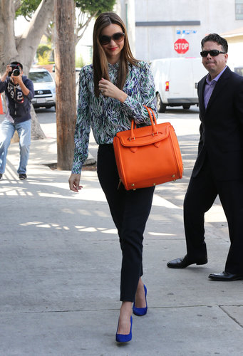 Miranda Kerr arrived at a meeting in West Hollywood wearing a blue-and-green printed Stella McCartney blouse with black cropped jeans, cobalt pumps, and a bright orange Alexander McQueen bag.