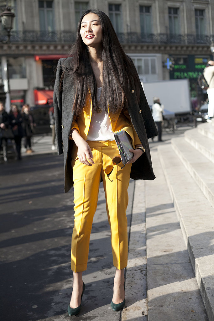 We love the cool color play at work here between the bright yellow, suiting, gray coat, and rich green heels.