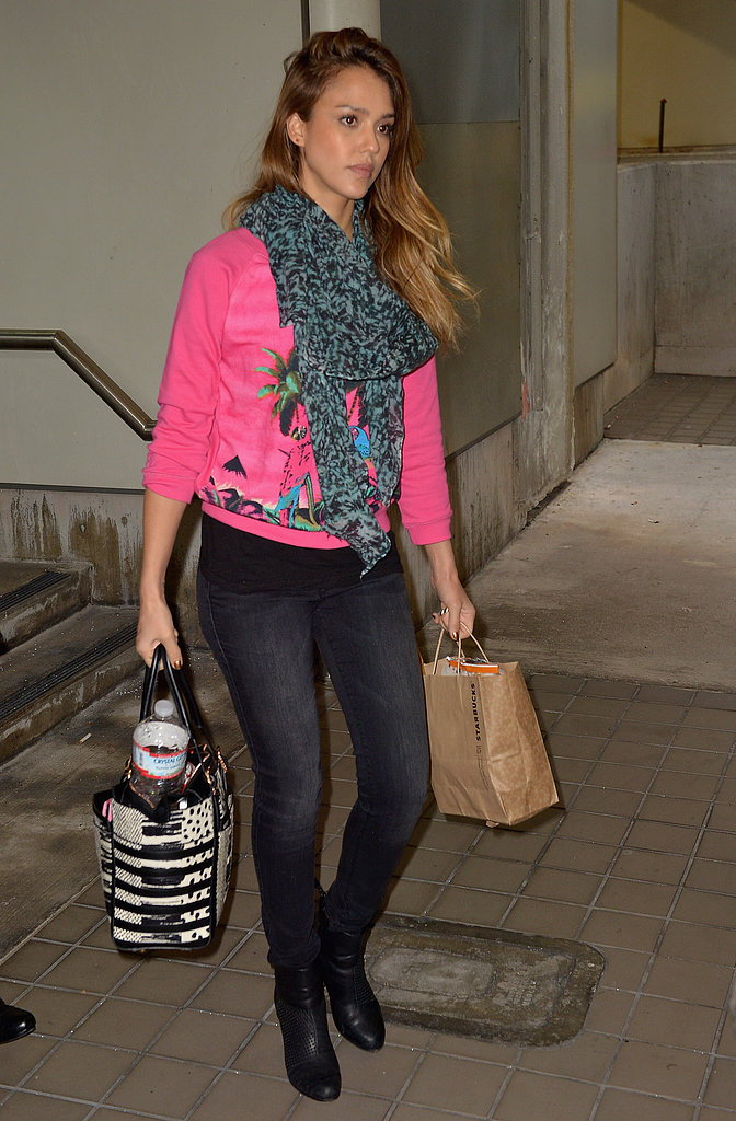 Jessica Alba arrived in Miami wearing a bright-pink printed sweater with a marbled scarf and her black-and-white Christian Louboutin bag.