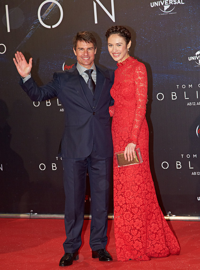 At the Oblivion premiere in Austria, Olga Kurylenko donned a red long-sleeved lace Valentino gown with a gold box clutch while posing with costar Tom Cruise.