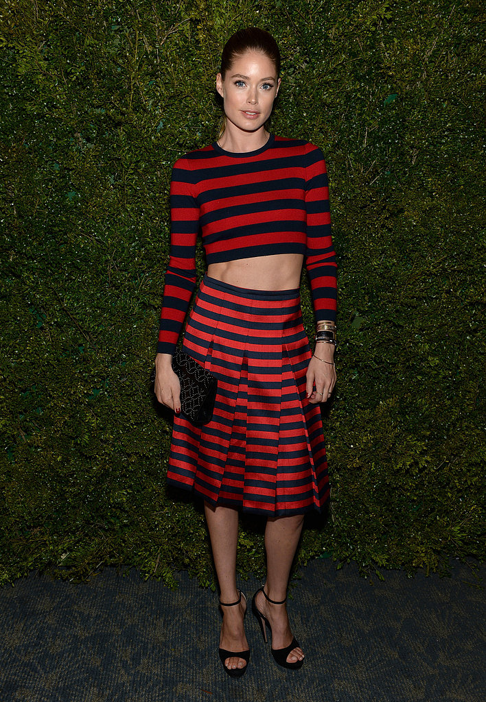 Doutzen Kroes showed off her enviable six-pack abs in a Michael Kors red-and-black striped crop top, pleated skirt, and black accompaniments.