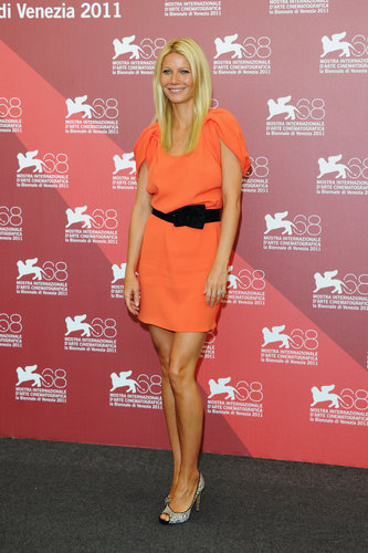Gwyneth embodied Spring in a cinched orange minidress and floral appliqué Nicholas Kirkwood pumps at a Contagion photocall in Venice.