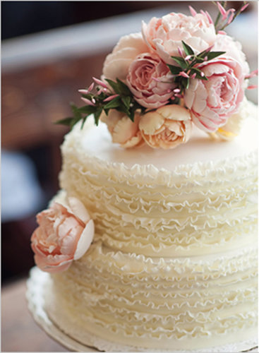 There's something so sweet about this simple but beautiful cake — the ruffles and flowers make a perfectly classic combo.  Photo by Oh, Darling! via Wedding Chicks