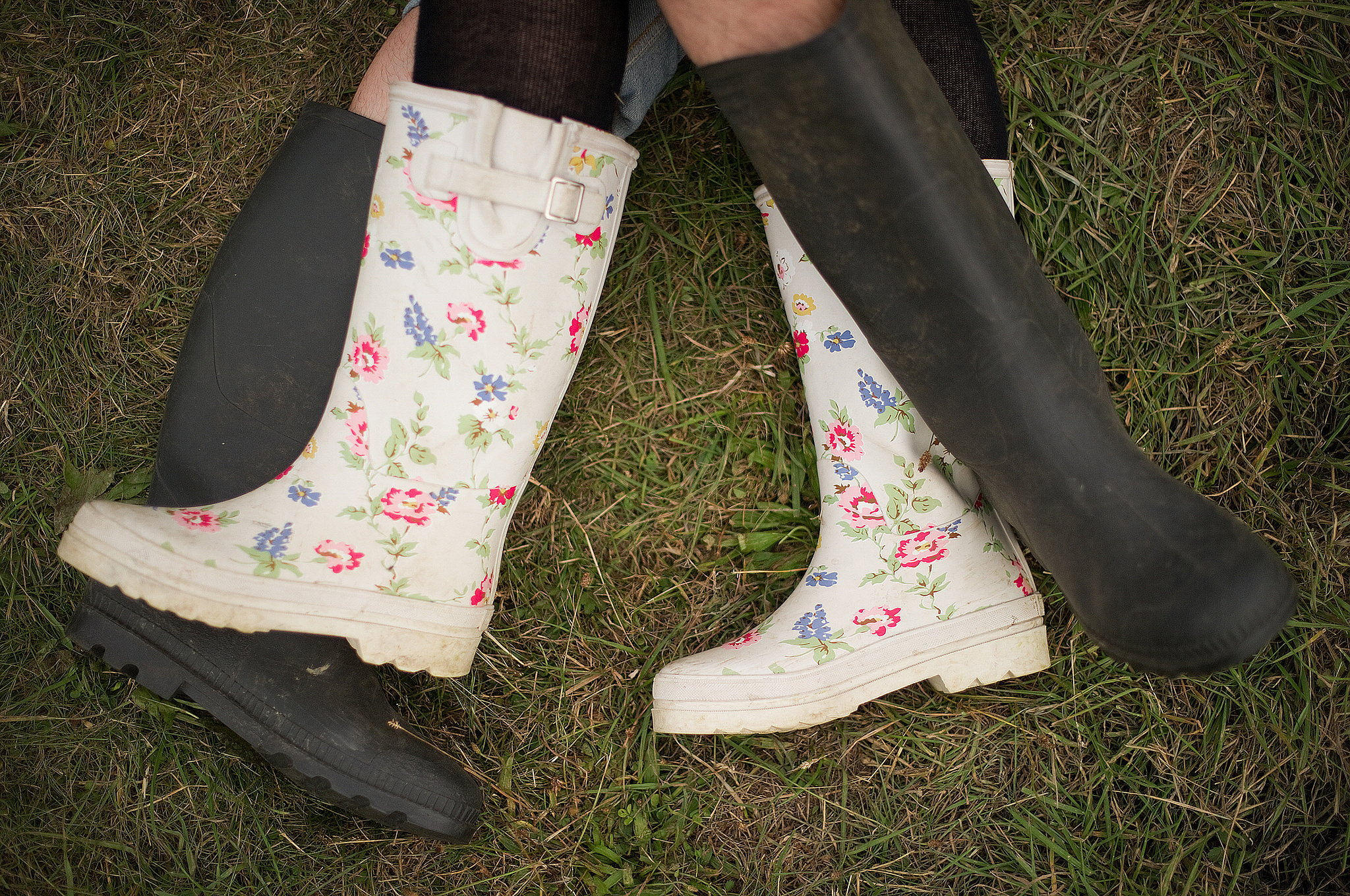 A couple in rainboots laid in the grass at the Big Chill festival near Ledbury in Herefordshire, England.