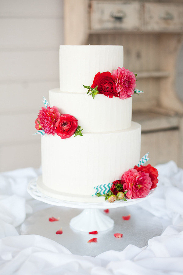 Breathe life into an uncomplicated white cake with bursts of color via bright flowers. It's an easy but oh-so-stylish way to upgrade your celebration.  Photo by Nancy Ray Photography via Style Me Pretty