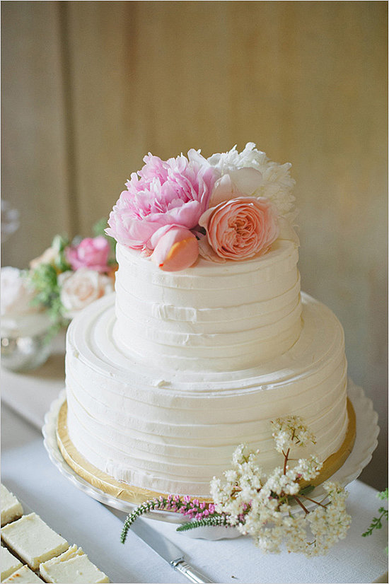 Top a buttercream-covered cake with pretty flowers, and voilà! Just like that, you've go yourself a fuss-free, beautiful dessert.  Photo by Delbarr Moradi Photography via Wedding Chicks