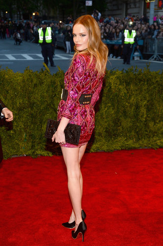 Kate Bosworth showed off her long legs in a bright pink beaded Balmain minidress, accessorized with a black studded belt, a beaded clutch, and black satin Ferragamo pumps.