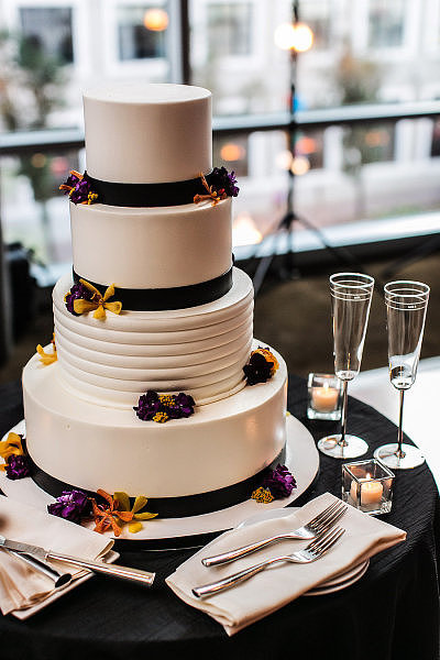 Black ribbon and a few bright flowers pop against the white frosting on this modern stunner.  Photo by Joshua Albanese Photography via Style Me Pretty