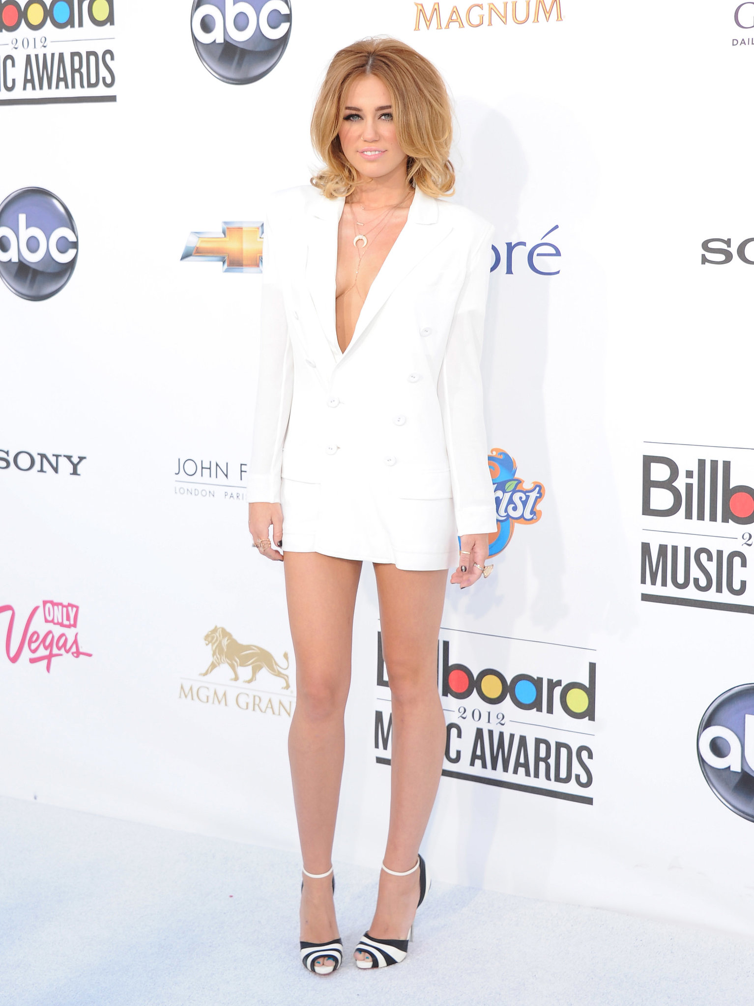Miley sexed things up for the Billboard Music Awards in May 2012, arriving in a crisp, white Jean Paul Gaultier button-down jacket (and little else). She spiced up the plunging neckline with a Jacquie Aiche gold body chain and a pair of black-and-white striped Christian Louboutin heels.