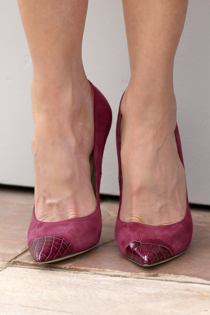 She offset the otherwise all-black look with cap-toe cranberry pumps that mixed suede with croc.
