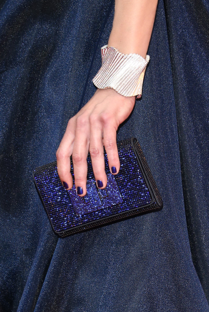 Milla Jovovich wore a thick silver bangle and carried a navy blue shimmering clutch.