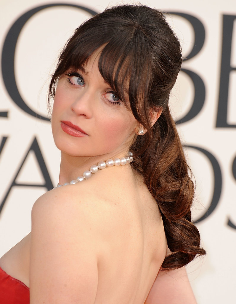 Zooey Deschanel rarely appears on a red carpet without her signature bangs, and this curly mid-height ponytail at the Golden Globes was no exception.