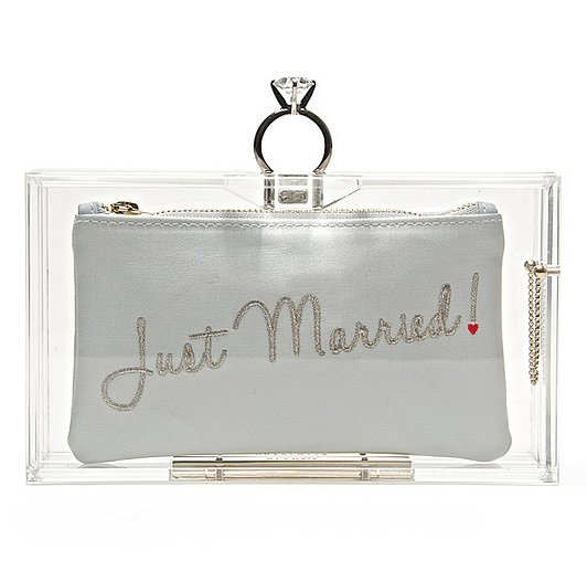 """Between the """"Just Married"""" inscription and the diamond ring clasp, we can't think of a more whimsical way to walk down the aisle than with this Charlotte Olympia lucite Marry Me Pandora clutch ($881)."""