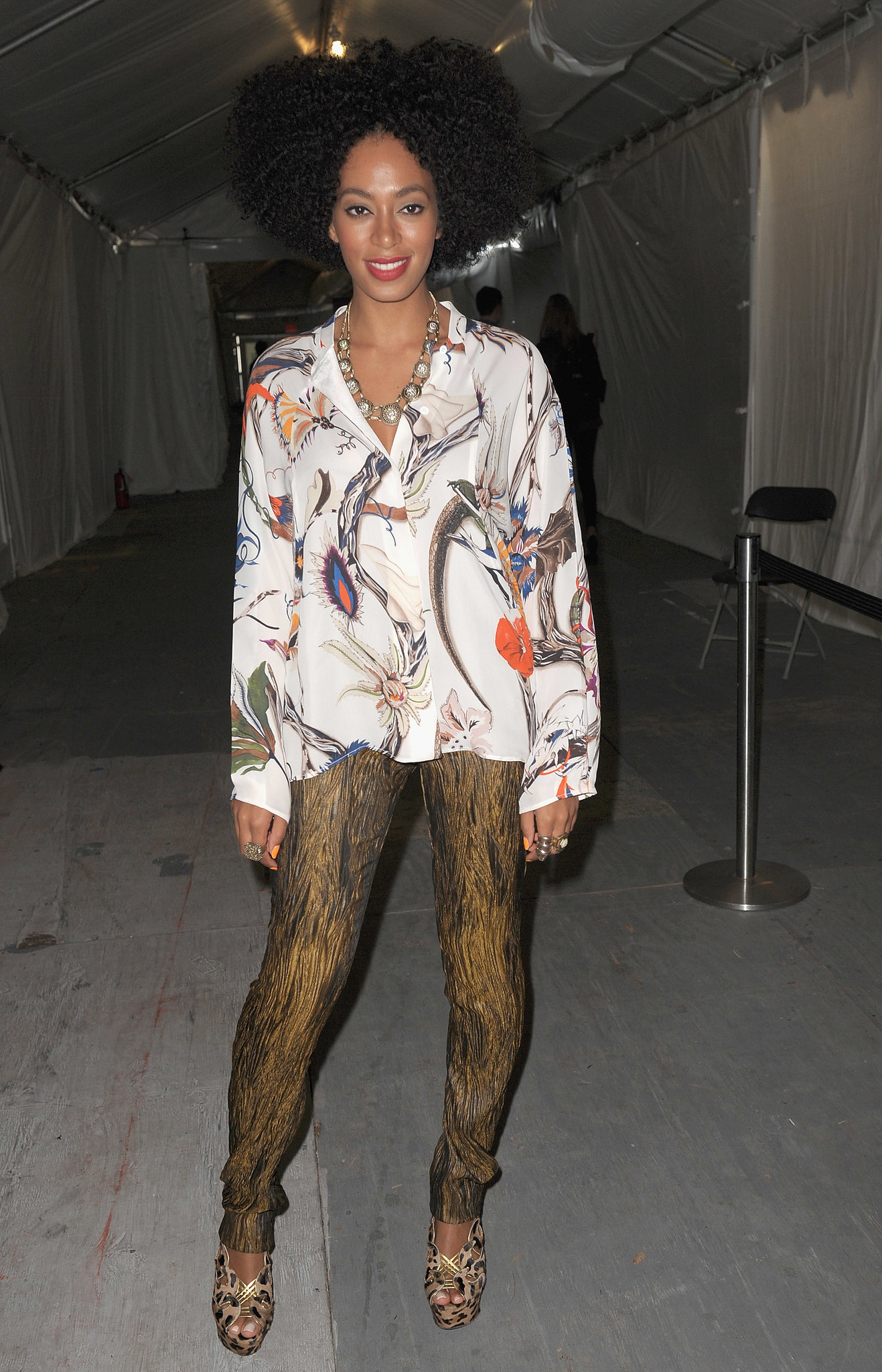 Solange styled her gold-and-black leggings with a floral button-down blouse and cutout leopard sandals during NYFW Spring 2012.