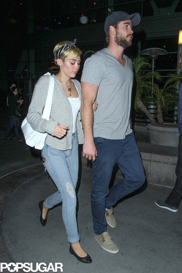 Miley Cyrus held on to her fiancé, Liam Hemsworth, for a movie date in LA.