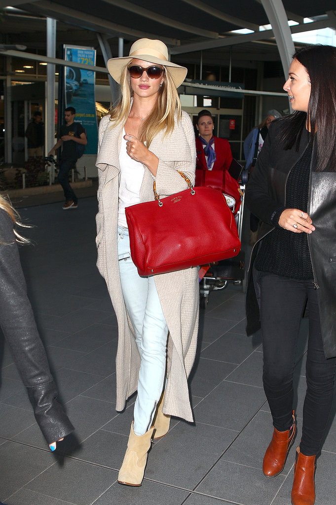 Rosie Huntington-Whiteley traveled in neutral and punchy hues when she paired a bright red bag with a tan floppy hat, tan booties, and a beige cardigan.