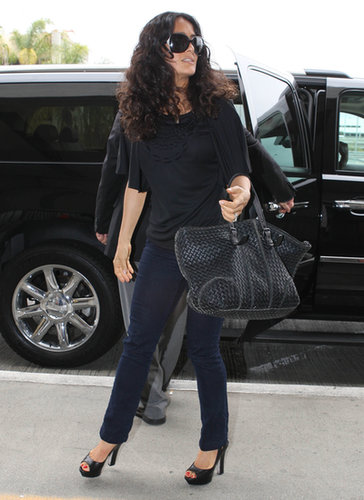 Salma Hayek went for all-black everything in her draped top, which she styled with sleek jeans, a pair of peep-toe pumps, and the ultimate carry-on: a Bottega Veneta bag.